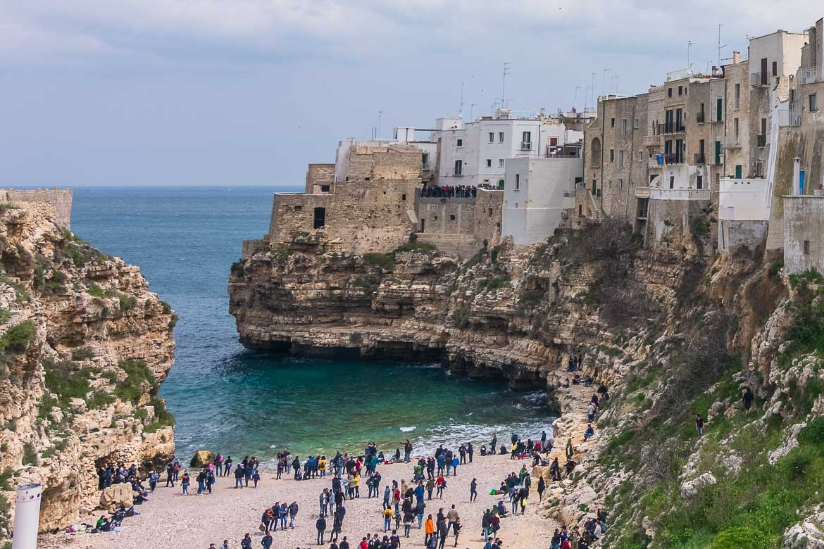 This is a panoramic view of Polignano a Mare. There are many people on the beach. The historic centre looms above in a gorgeous way.