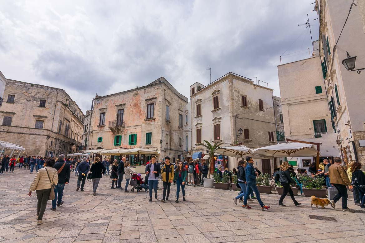 This photo shows what to do in Polignano a Mare on a busy day. People watch at Piazza Vittorio Emanuele II! The square is lined with gorgeous old buildings. There are many people walking around.