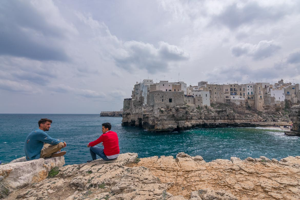 This photo shows two men sitting on the edge of Pietra Piatta, the flat rock. In the background, the gorgeous Old Town of Polignano a Mare stands atop a limestone cliff.