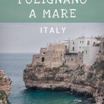 This image shows the beach in Polignano a Mare with the historic centre hanging on the limestone cliff above. There are many people standing or sitting on the pebbles gazing at the emerald sea. It's a cloudy spring day. This is an optimised image for Pinterest. There is overlay text that reads: What to do in Polignano a Mare Italy. If you like our article, please pin this image.