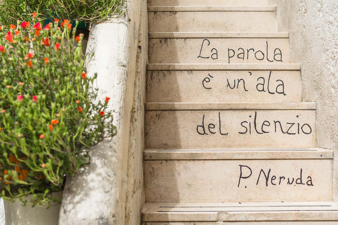 This is a photo of Poetry Steps Polignano a Mare. There's a verse from P. Neruda's Sonnet 44 written on the steps: la parola è un'ala del silenzio. This translates to: the word is a wing of silence.