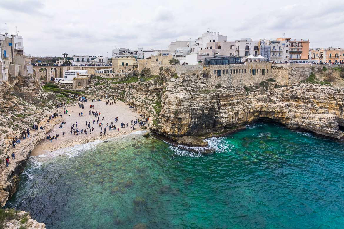 This is a panoramic view of Polignano a Mare. It was shot from Terrazza Santo Stefano, the most popular viewpoint in the town. We can see the beach with the dramatic cliffs above it. It's a cloudy spring day.