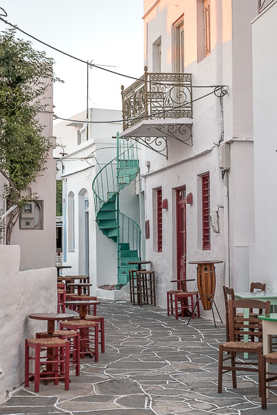 This photo shows a quaint alley in Apollonia. There are traditional buildings on both sides of the street. TAbles and chairs are placed near the walls.