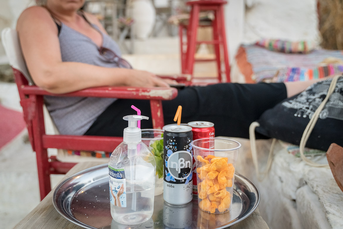 This is a close up of a tray containing drinks, snacks and a large hand sanitizer. The tray sits on an outside table at Cavo Sunrise bar. In the background, Maria waits to drink her cuba libre.