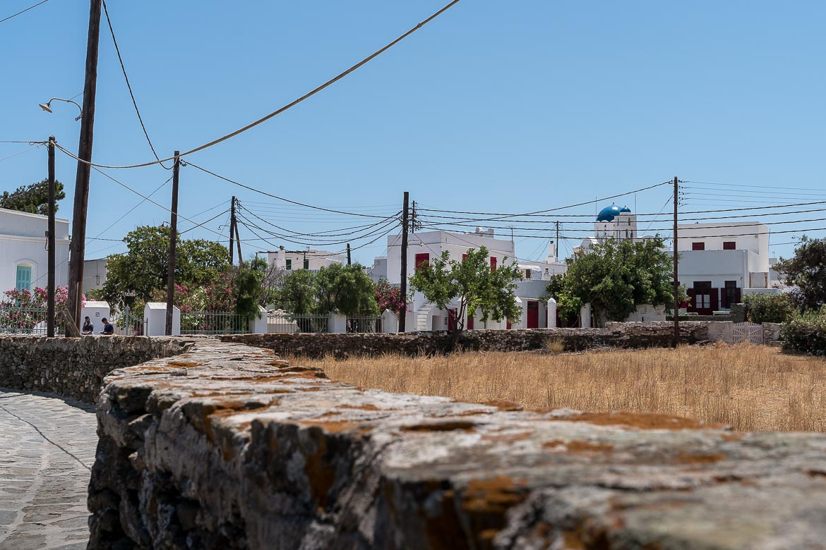 This photo shows the white buildings of Exambela Village from a distance. In the foreground, a glorious dry stone wall.