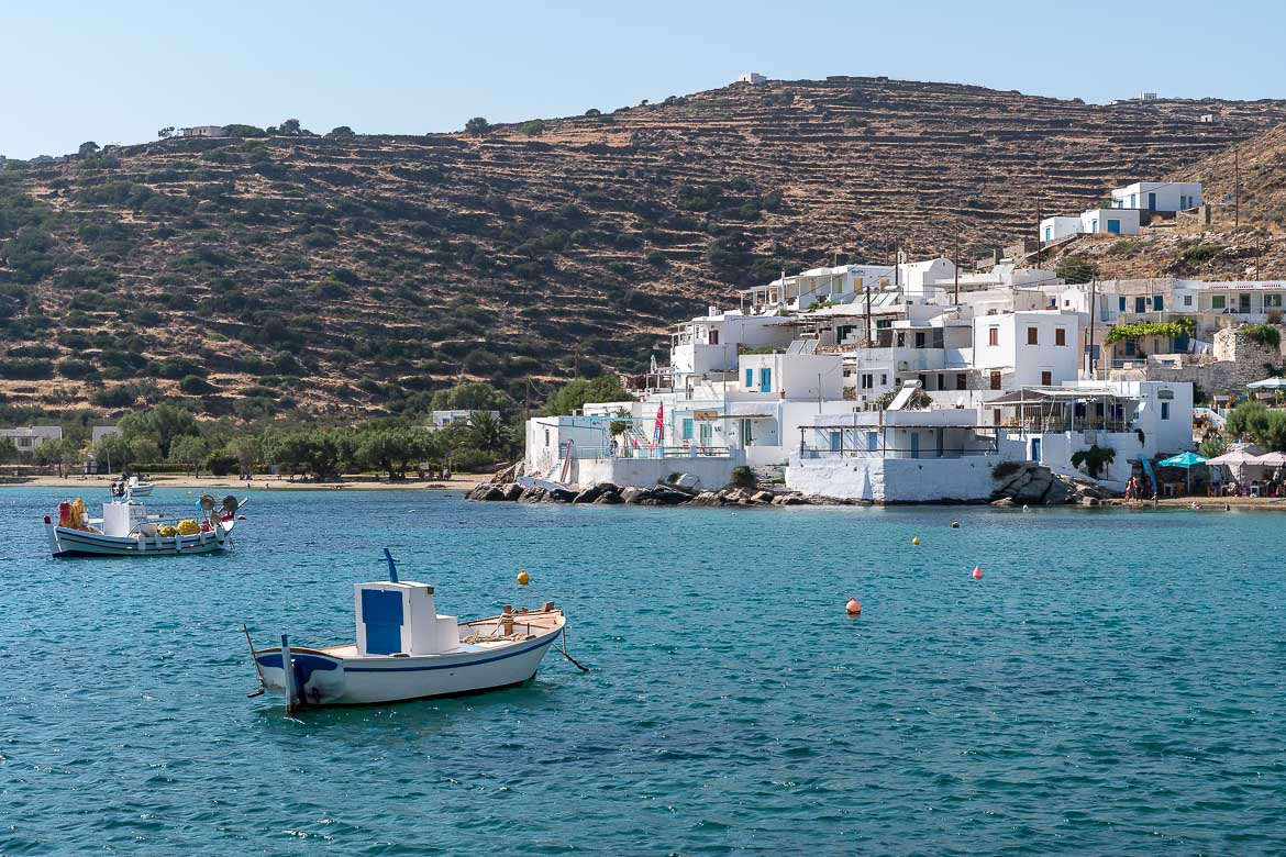 This is a panoramic shot of Faros village. The all-white village is amphitheatrically built and the last houses almost touch the sea. In the foreground, a traditional fishing boat.