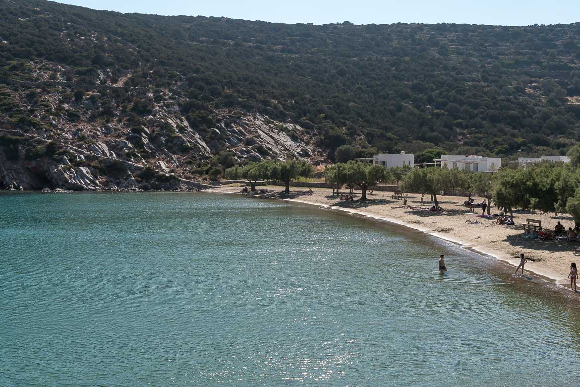 This is a panoramic view of Glifo Beach. It is a sandy beach with trees surrounded by rocky hills.