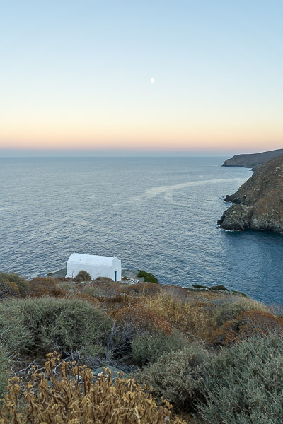 This photo shows a small whitewashed church on a slightly steep slope above the sea.