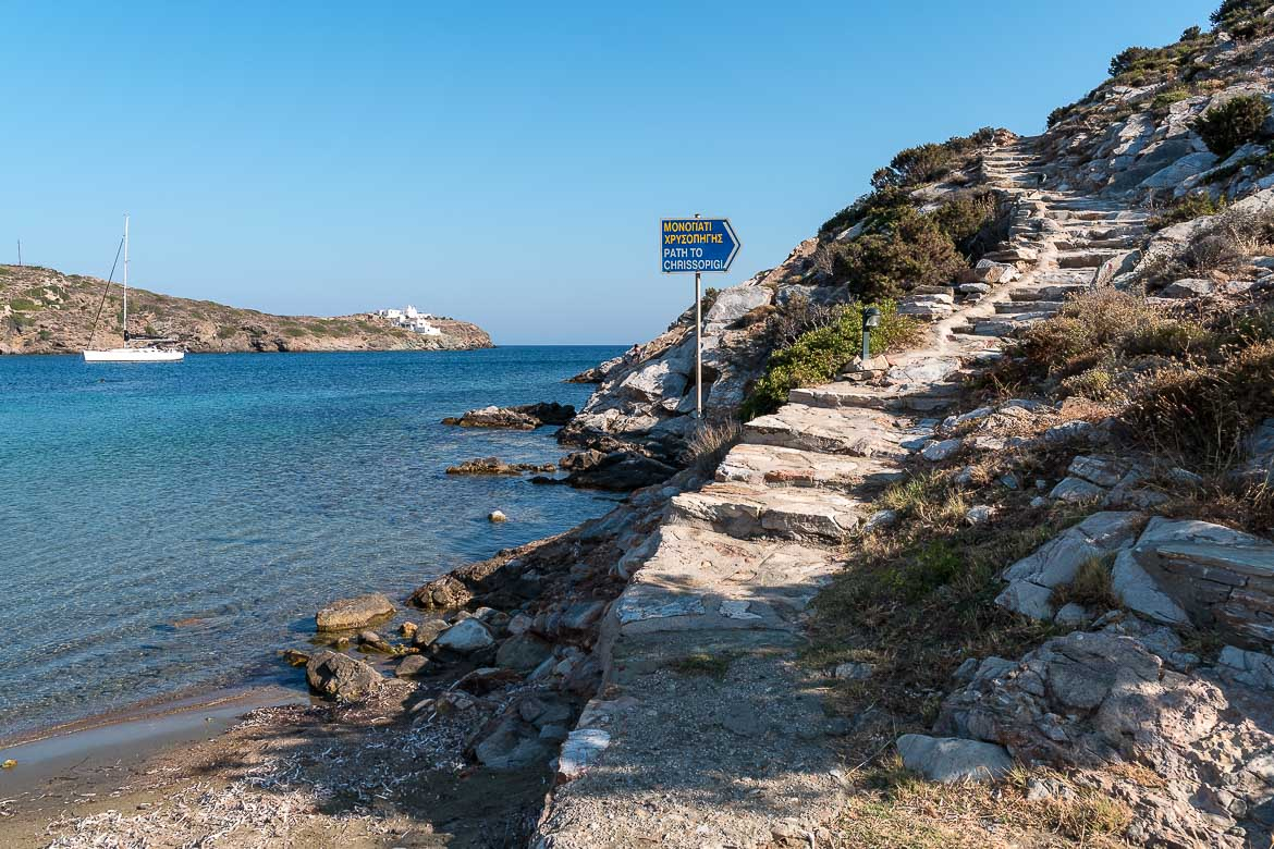 This photo shows The starting point of the path that leads from Glifo Beach to Chrissopigi Monastery. It is a slightly uphill paved path with fantastic views to the sea. If you're wondering what to do in Sifnos, hiking is a great option!