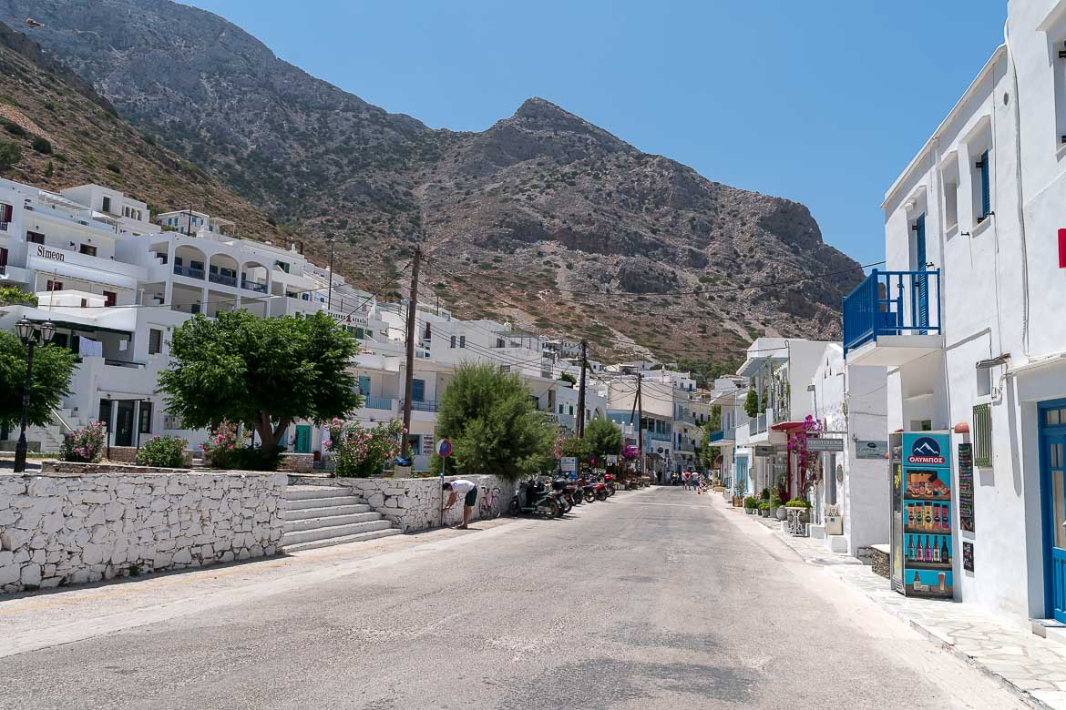 This photo shows The main street at Kamares Port. It's lined with shops and restaurants.