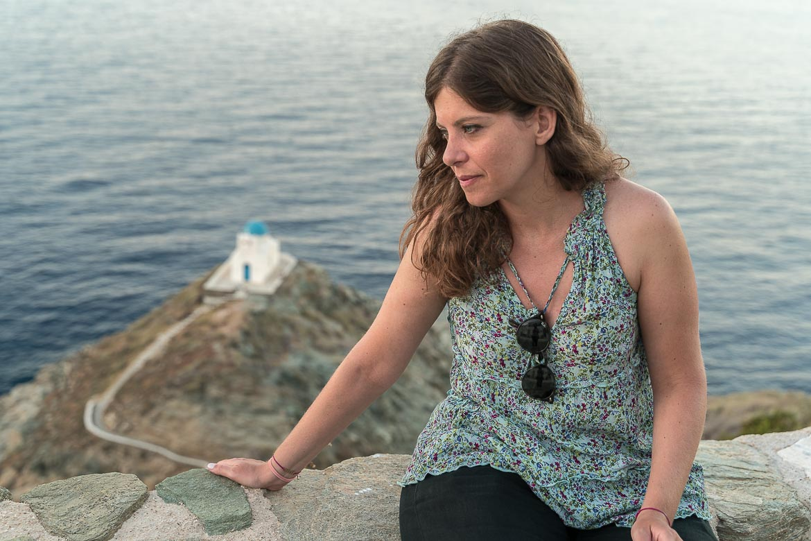 This photo shows Katerina posing in front of the Seven Martyrs Church. She is wearing a light blue floral top and she is looking towards the sea.