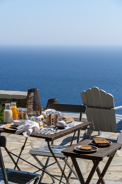 This photo shows a table set for breakfast at Verina Astra. There are many delicious treats on the table. The view to the sea is just amazing.