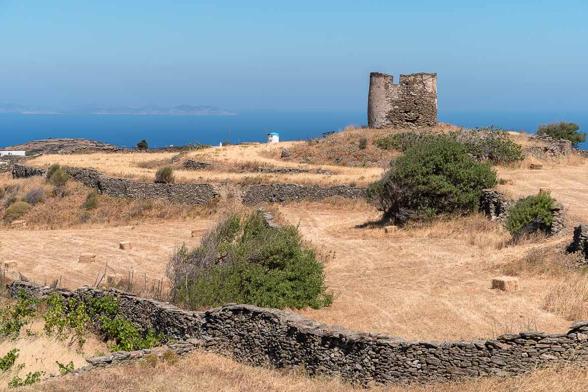 This image shows one of the island's round stone watchtowers. It is built on a low hill surrounded by low vegetation and dry stone walls. In the background, the sea and a white windmill.