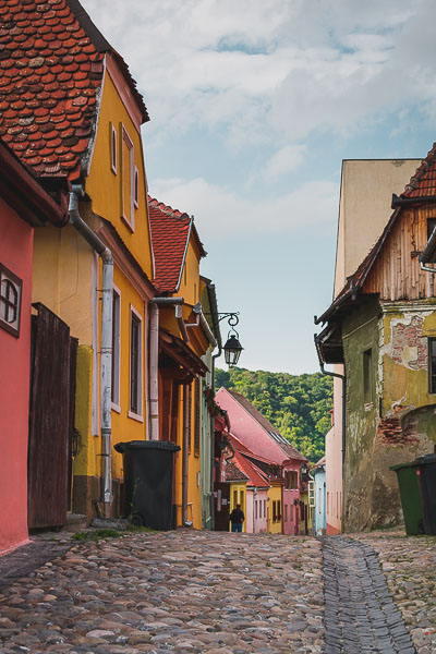 A picturesque stony lane lined with colourful buildings in the heart of Sighisoara Citadel Transylvania. What to do in Sighisoara Romania in 24 hours.