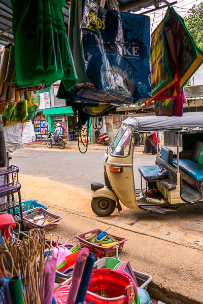 This photo was shot from inside a store at Trincomalee market. There are items hanging from the ceiling. There is a tuk tuk parked outside.