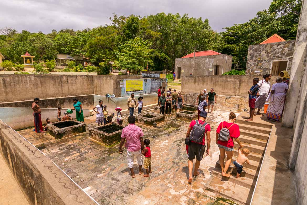 This photo shows the Kanniya hot springs. There are many people, locals and tourists alike. They are all barefoot.