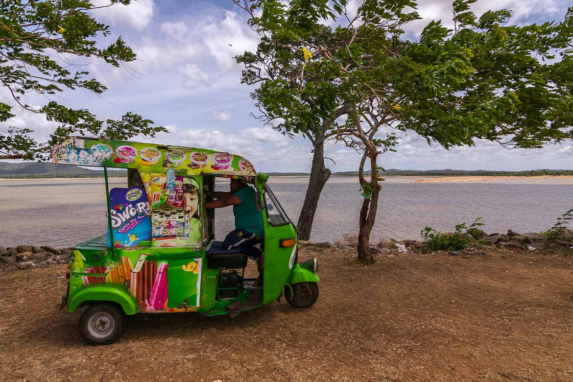 This photo shows the view to Kantale Tank. In the foreground, a colourful tuk tuk selling ice cream.