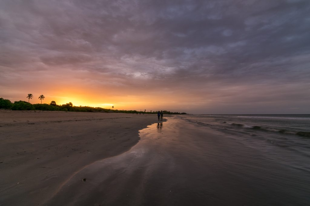 This photo shows Nilaveli Beach at sunset. There are two people walking on the sand and the sky is cloudy. Yet there are beautiful yellows and oranges in the sky. We chose this photo to be the featured image of our article What to do in Trincomalee Sri Lanka in 2 days.