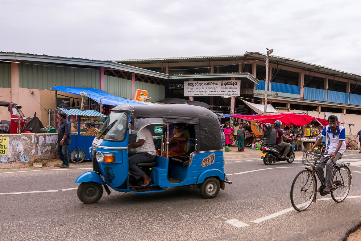 This photo was shot at one of Trincomalee's main roads. There are a couple of shops in the background. In the foreground, a tuk tuk, a bicycle and a motorbike move on the road.