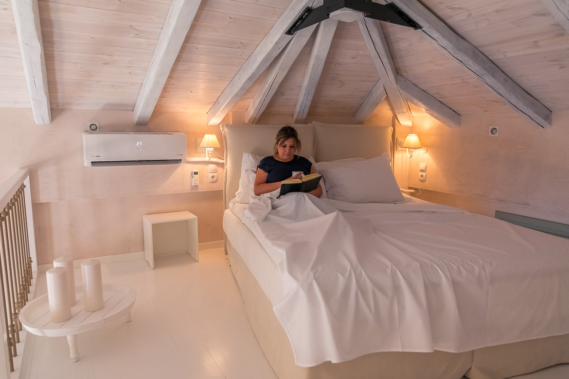 This is a photo of Maria reading a book in her all white bedroom at Chroma Pelion Villas.