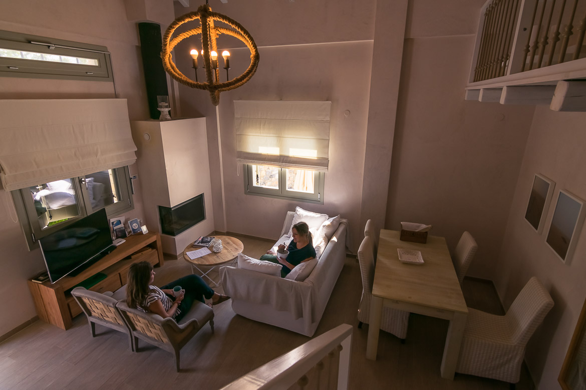 This image shows Katerina and Maria sitting at the living room in the villa having breakfast and chatting.