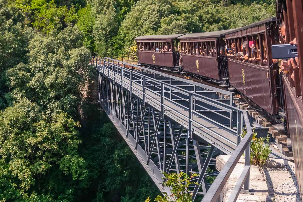This image shows the Pelion Train crossing the De Chirico Bridge. The iron bridge is straight but the wooden rail tracks are curved. People on board the train look out of the windows and take pictures.