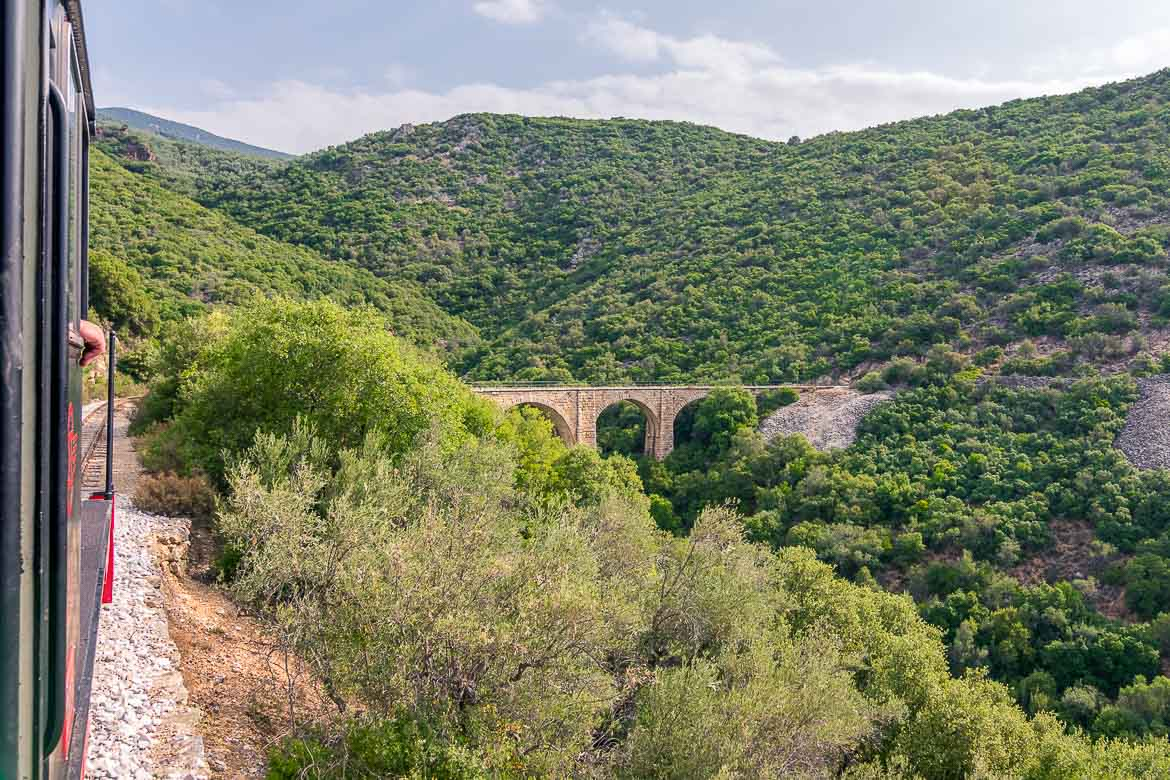 This photo shows Kalorema Bridge amid lush greenery. The picture was shot from on board the Pelion train.