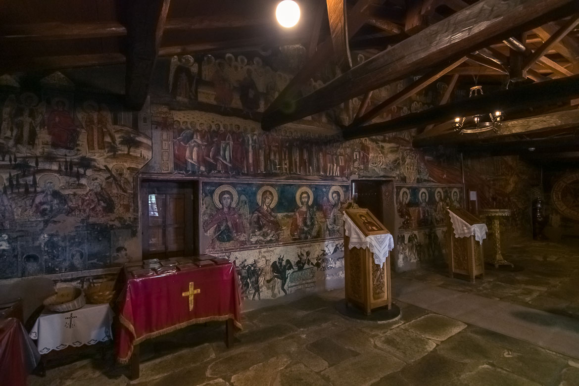 This photo shows the interior of St Taxiarchis & All Saints Church. There are many very well preserved frescoes on the walls which deppict saints in vivid colours.