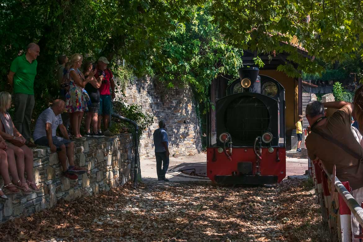 This photo shows the locomotive of the vintage Pelion Train on the turntable. It is ready to be turned to the opposite direction so that it starts its journey back to Volos. There are many people looking and taking photos.