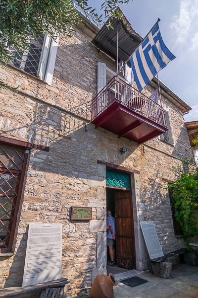 This photo shows the facade of the Olive Museum in Ano Gatzea. The museum is housed in a traditional stone building.
