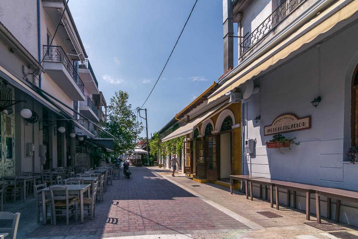 This image shows a pedestrianised street at Palia District in Volos at noon. The street looks absolutely calm, almost deserted because it is in the evening that this area comes to life. If you are wondering what to do in Volos at night, Palia is the place to be.