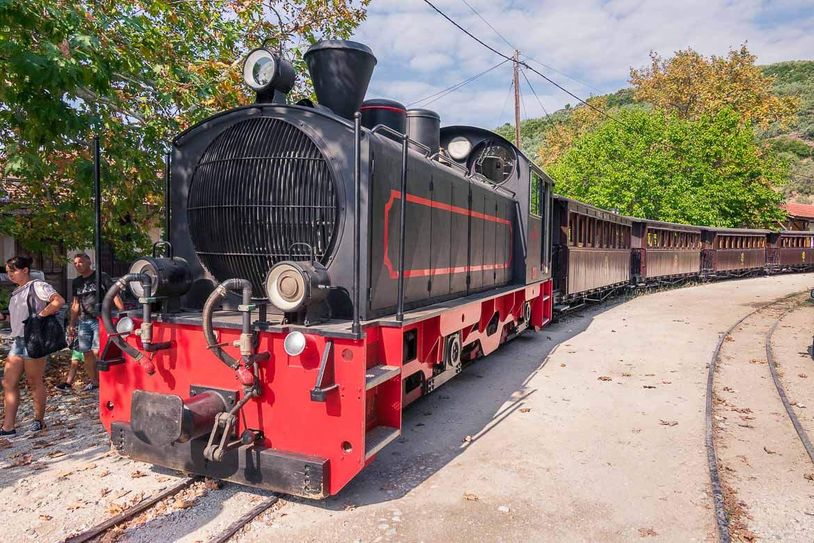 This image shows the vintage Pelion Train at Ano Gatzea station. The locomotive is red and black in colour while the railcars are brown.