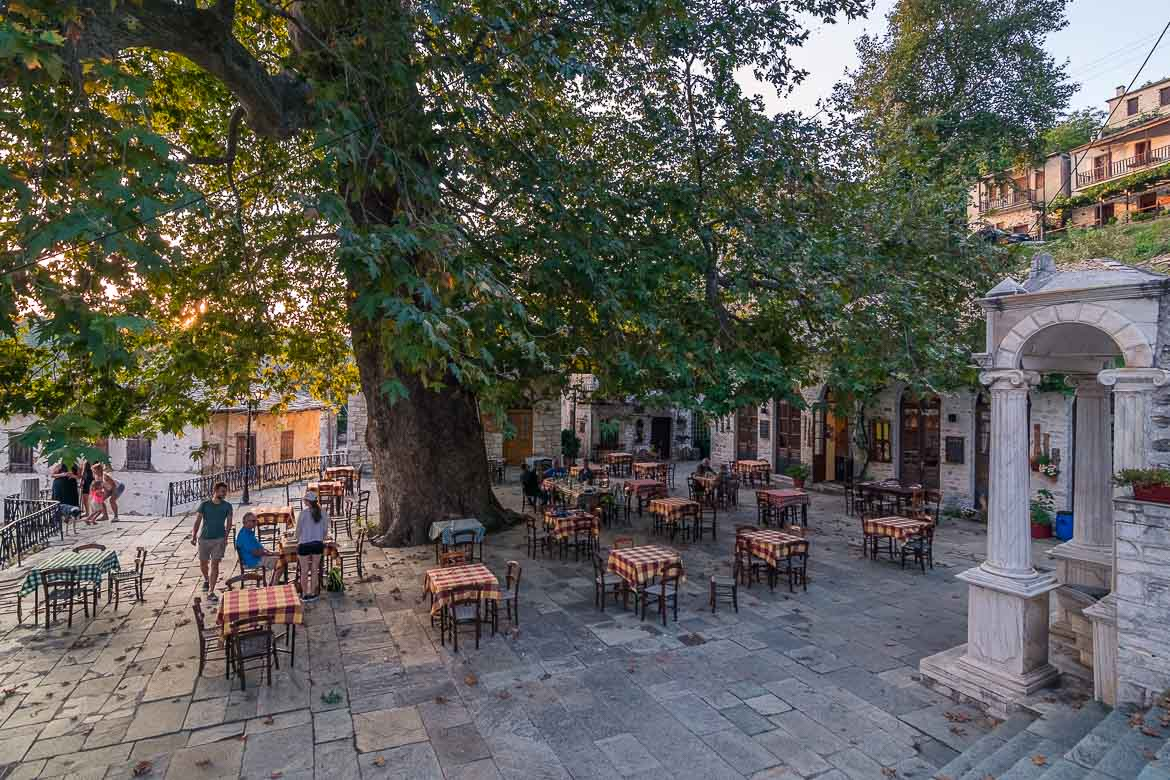 This image shows the main square at Pinakates Village. There are many tables with checkered tableclothes under the shade of an enormous plane tree. At the right hand side, there is a beautiful marble fountain.