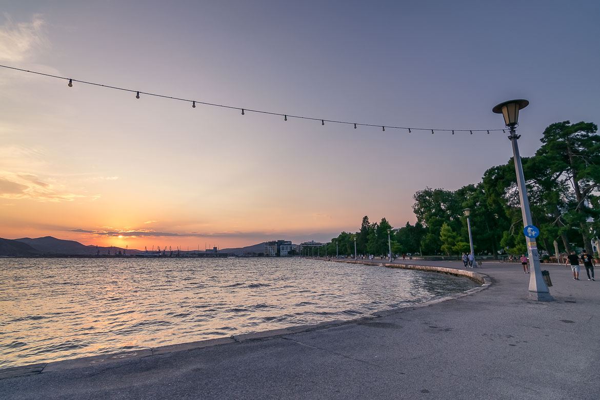 This image was shot at the seaside promenade at sunset. There are people walking along the seafront promenade. In the background, a gorgeous sunset above the port of the city.