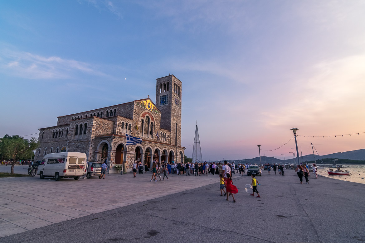 This is an image of St Constantine church at sunset. The church is at the seafront. There are many people standing outside the church.