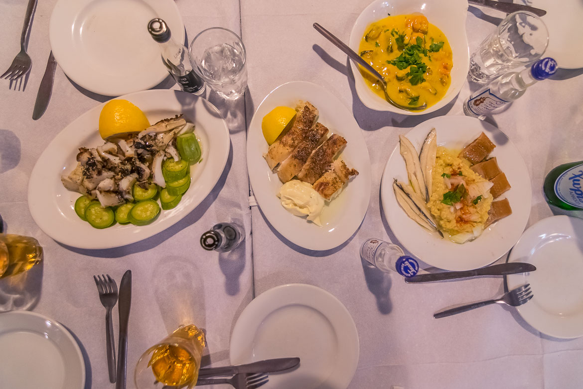 This is a close up of a table filled with seafood dishes and little bottles of tsipouro.