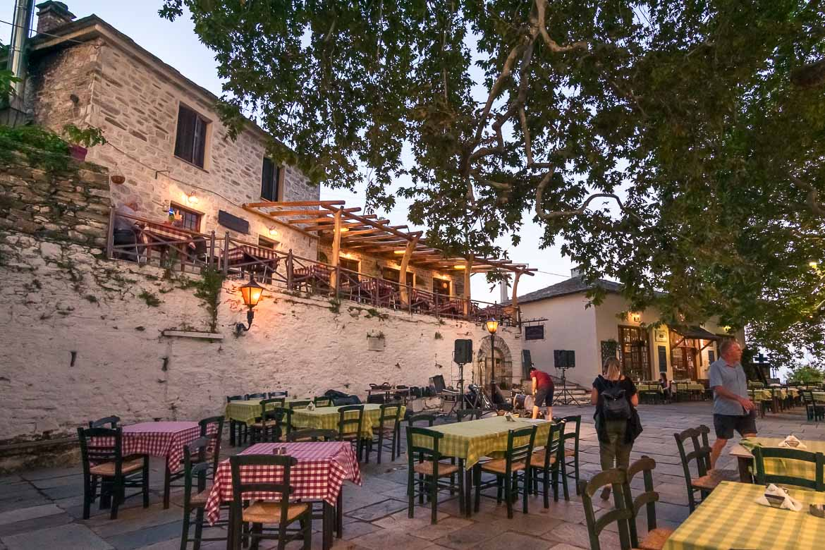 This is an image of the main square in Vyzitsa, Pelion at dusk. There are tables with checkered tablecloths under a huge plane tree. Maria and a couple of other people wander around the square.