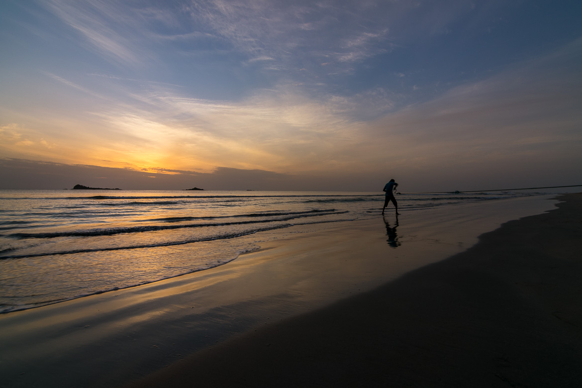 This is a photo of Nilaveli Beach at dawn. There is no one around except for a fisherman pulling his nets.