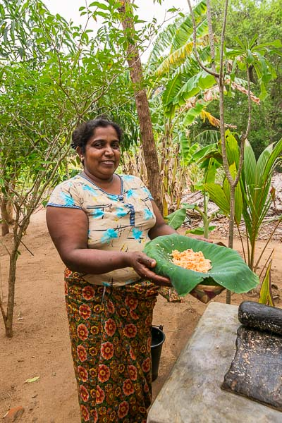 This photo shows a Sri Lankan lady who has just prepared a traditional local dish for us to try. She is holding a cane plate covered in banana leaves and that's where the food is served. She is smiling and kind.