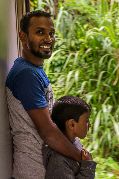 This is a close up of a smiling dad holding his little boy on board the train from Kandy to Ella.