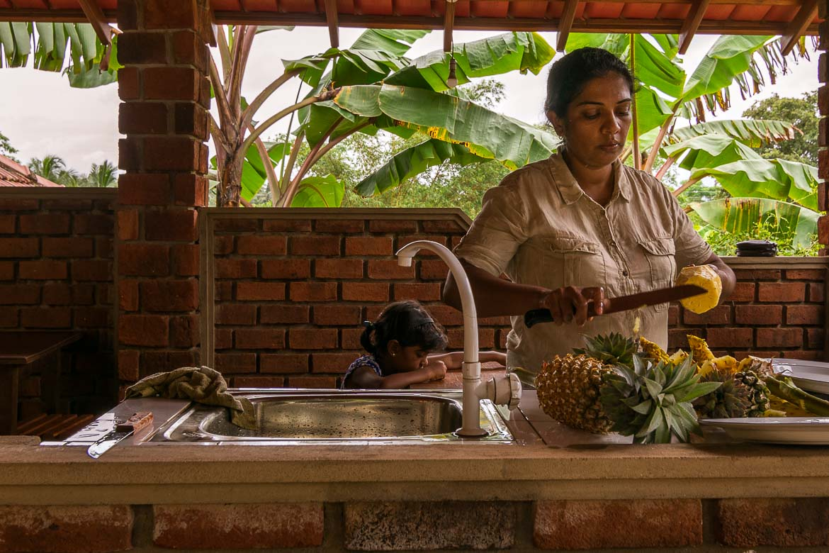 This photo shows a local lady cutting pineapple and other fruit for us. We are at the Pineapple Village in Kudagammana.