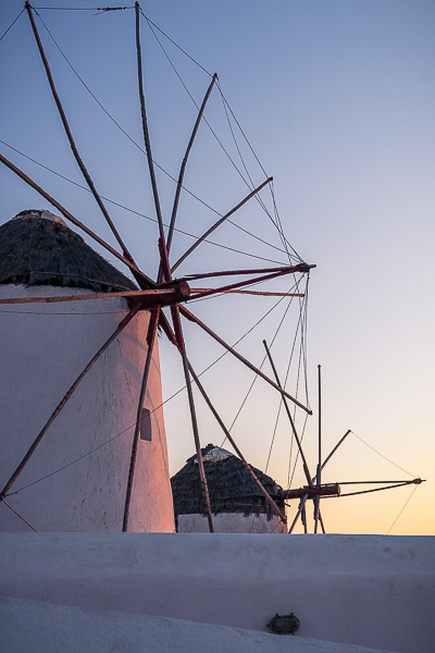 This is a close up of two of the famous Mykonos windmills. There is red colour reflecting on their surface because it's sunset.