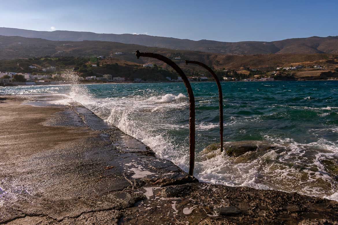 Nimporio Port in Andros Town on a windy day. The sea is fierce and water covers the dock. 13 unique things to do in Andros Greece and full Andros Guide.