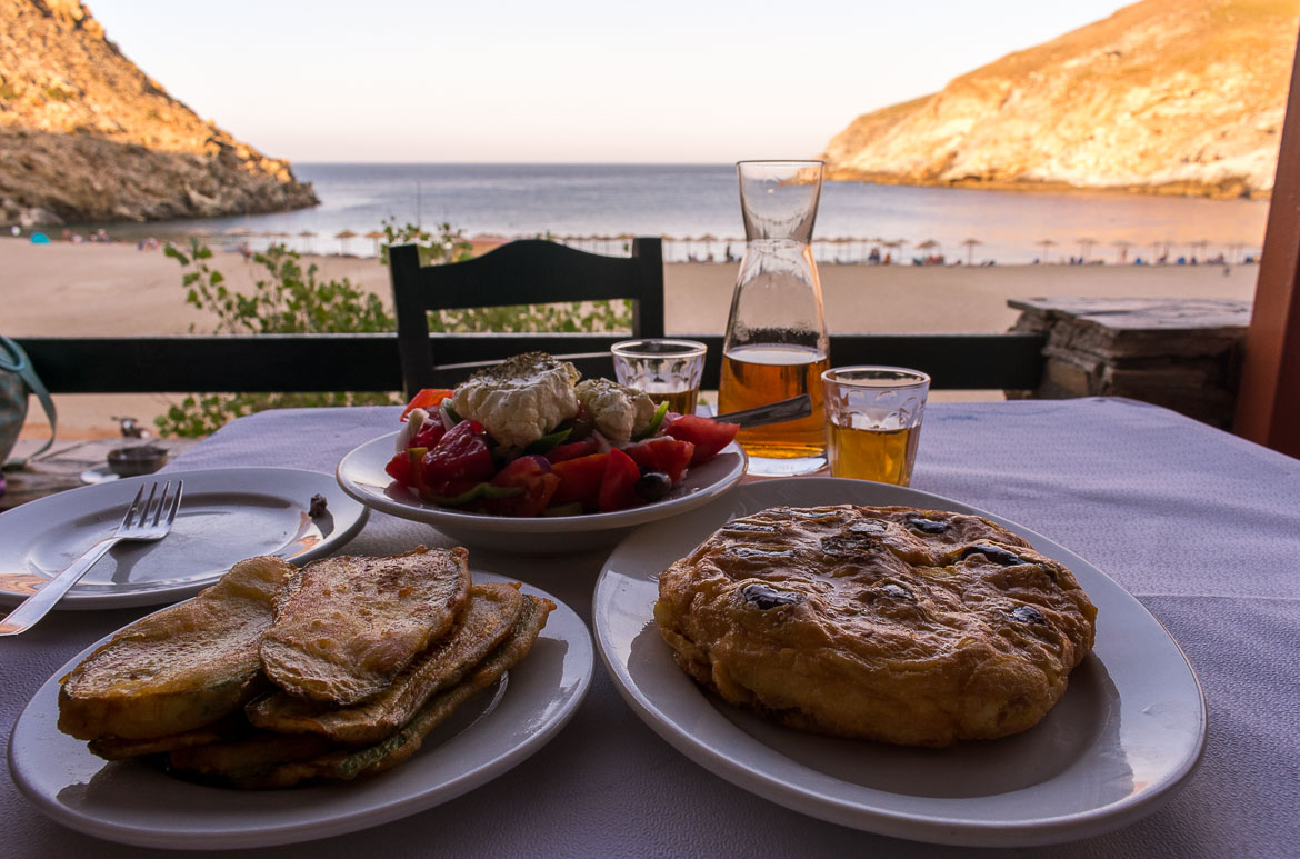 Fourtalia, Greek Salad with local cheese and exquisite homemade wine at Zorgos Tavern. In the background, Zorkos Beach at sunset.